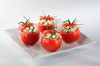 Tomatoes stuffed with pieces of ewe cheese with aromatic herbs