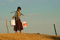 A young girl coming bach home with water, village of Banteay Chhmar, Cambodia