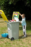 Young boy throwing paper in a recycling container