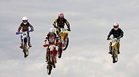 Four jumping motocross riders