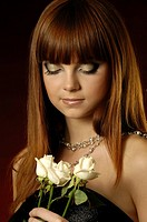Romantic young woman with chestnut_coloured hair and make_up holding three white roses