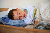 Boy lying in a bed and reading