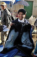 Child labour, 10-year-old boy selling trousers on El Alto market, La Paz, Bolivia, South America