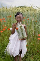 African girl holding insect jar