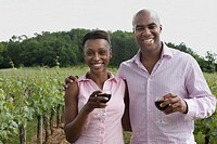 African couple holding wine glasses in vineyard