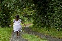 African girl in fairy costume running down remote road
