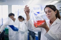Mixed race scientist working in laboratory with beaker of liquid