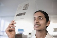 Indian scientist looking at transparency in laboratory