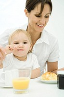 Professional woman sitting at breakfast table, toddler sitting on lap, spoon in mouth