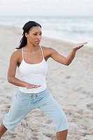 African woman practicing yoga at beach