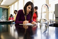 Hispanic teenage girl studying in chemistry lab