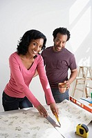 African couple measuring wallpaper