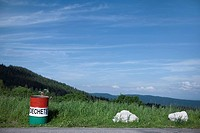 Garbage can on side of road overlooking rolling landscape