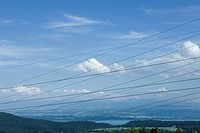 Cables criss-crossing in front of scenic landscape
