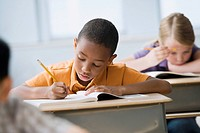 African boy writing in workbook in classroom