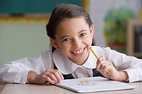 Hispanic girl writing in notebook in classroom