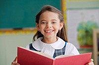 Hispanic girl reading from book in classroom