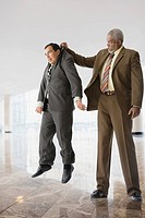 Tall businessman lifting short businessman