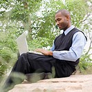 African businessman typing on laptop in park