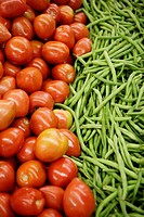 Tomatoes & green beans on display in market.