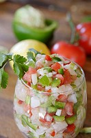 Close-up of large glass filled with Ceviche. Lemon, pepper & tomatoes in background.