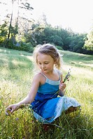 Girl picking wildflowers in meadow