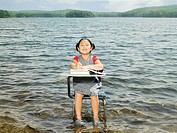 A girl sat at a desk in a lake (thumbnail)