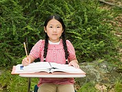 A girl sat at a desk in a forest