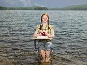A girl sat a desk on a lake