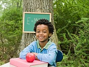Portrait of a boy sat at a desk in a forest