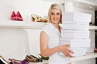 Woman holding a stack of shoe boxes