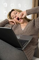 Yawning woman with laptop