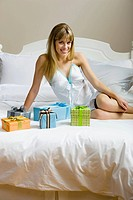 A woman sitting on a bed with presents