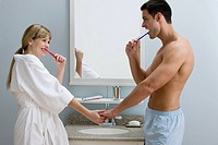 A couple holding hands whilst they brush their teeth