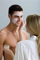 A woman applying face mask to a mans face