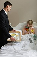 A man handing an ill woman soup
