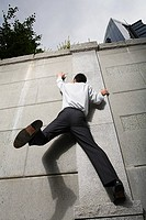 Businessman climbing wall