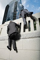 Businessmen climbing wall
