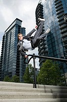 Businessman swinging on railing