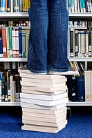 Student standing on books in library