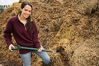 Woman moving a mound of straw