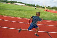 A young boy runs on a track preparing for competition