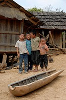 Everyday life in poverty for the Hmong minority, children standing behind the shell of an american bomb from the Vietnam war used as a cattle watering...