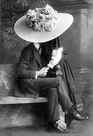 Young pair kissing under a giant hat, historical photo, circa 1910
