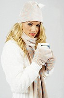Young woman dressing in winter clothing warming up with a cup of hot tea
