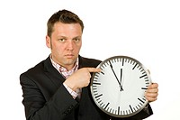 40-year-old businessman pointing at a clock, time is 5 to 12