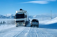 Truck and car driving along a snow_covered circular road near Hoefn, southern coast of Iceland, Europe