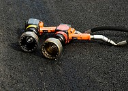 Two hydraulic wheel change impact wrenches, air guns for Formula 1 cars lying on the asphalt, Barcelona Spain
