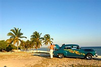 Vintage car parked a palm-lined beach, Playa Giron, Cuba, Caribbean, Americas