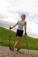 Young woman Nordic walking ski walking